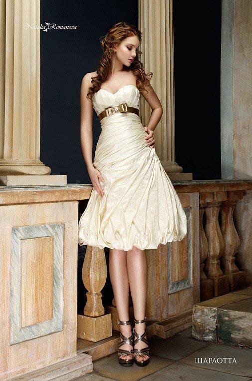 Стильное свадебное платье длиной до колена, из фактурной золотой ткани с драпировками.