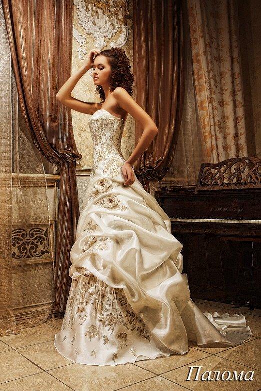 Необычное свадебное платье с золотистой отделкой и пышным длинным шлейфом.