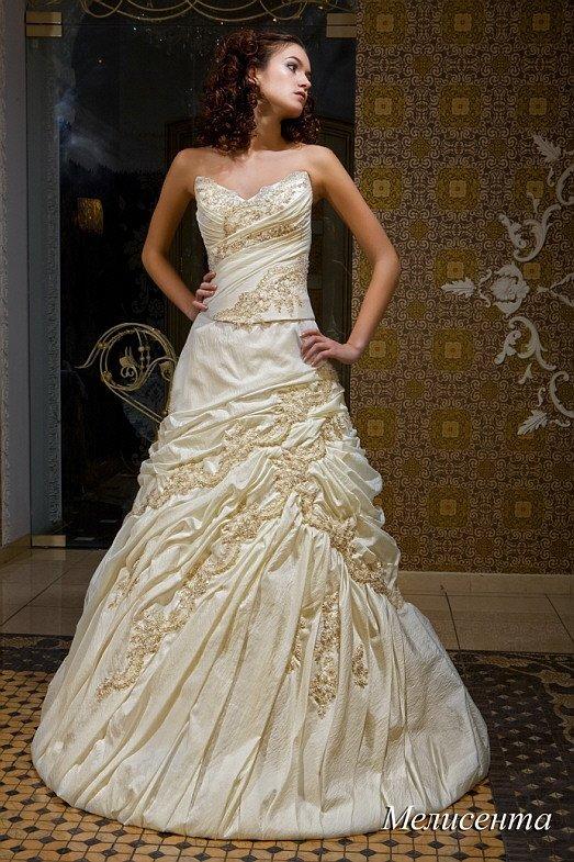 Драматичное свадебное платье цвета слоновой кости, с открытым лифом и декором из драпировок.