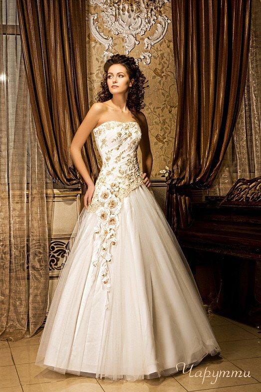 Стильное свадебное платье «принцесса» с золотистым кружевом отделки и многослойной юбкой.