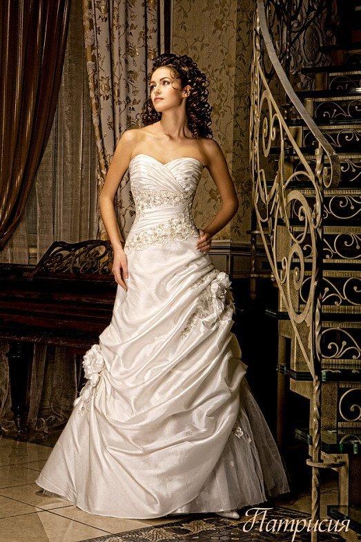 Свадебное платье «принцесса» с драматичной отделкой из драпировок и открытым декольте.