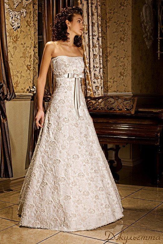 Свадебное платье с кружевной отделкой и завышенной талией, выделенной атласным поясом.