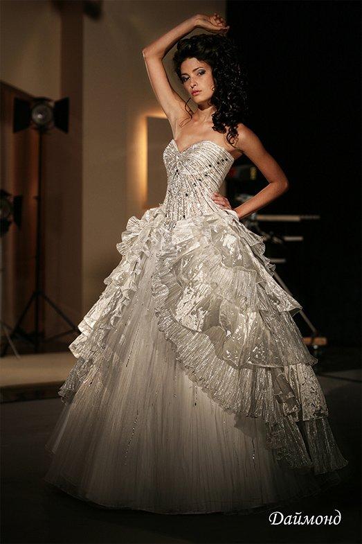 Сияющее свадебное платье с причудливыми оборками по юбке и фактурным корсетом со стразами.