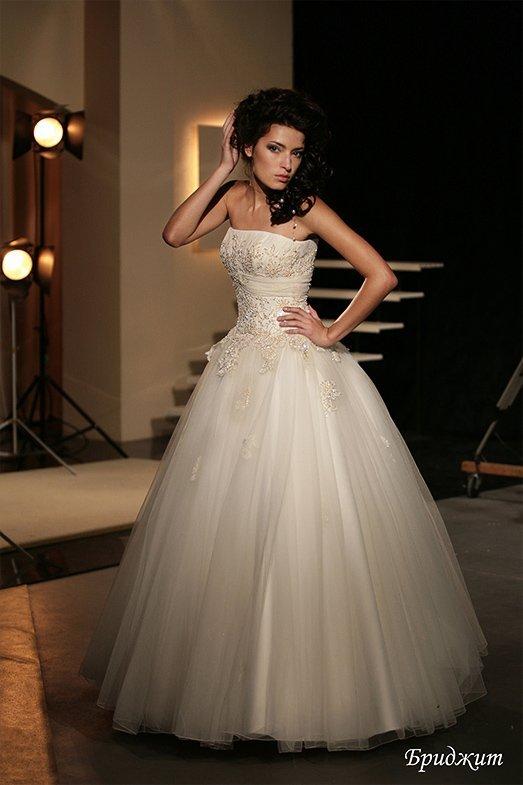 Пышное свадебное платье с открытым лифом прямого кроя и романтичным кружевным декором.