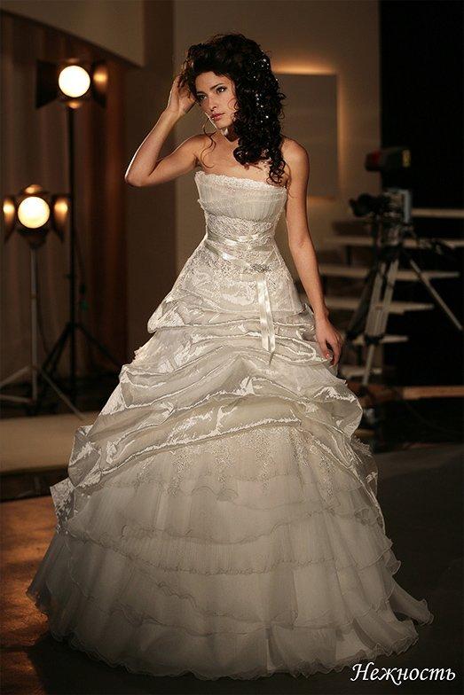 Открытое свадебное платье пышного кроя с атласным поясом и глянцевыми оборками по юбке.