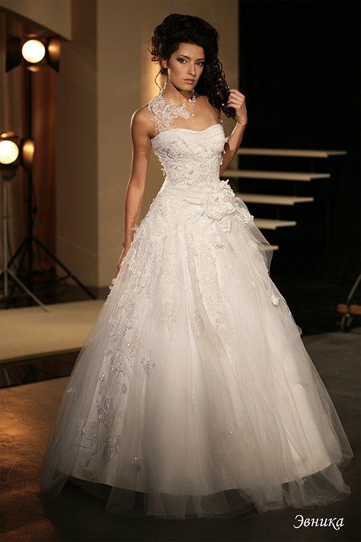 Необычное свадебное платье пышного кроя с объемным декором и кружевной бретелью.