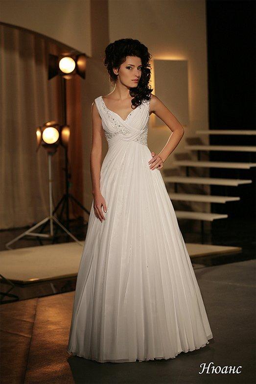 Изящное свадебное платье с V-образным вырезом и многослойной юбкой пышного кроя.