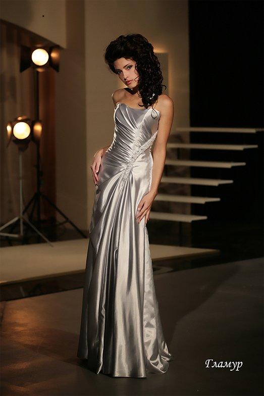 Изысканное свадебное платье серебристого оттенка с открытым верхом и декором из драпировок.