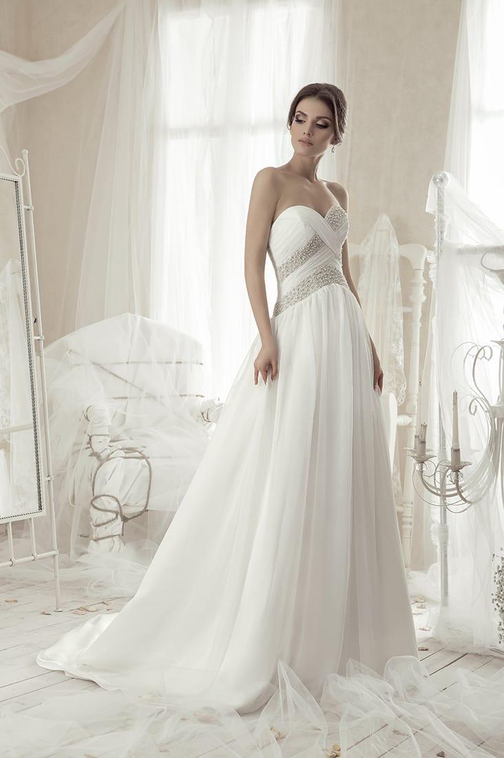 Лаконичное свадебное платье с открытым лифом и драпировками на корсете.