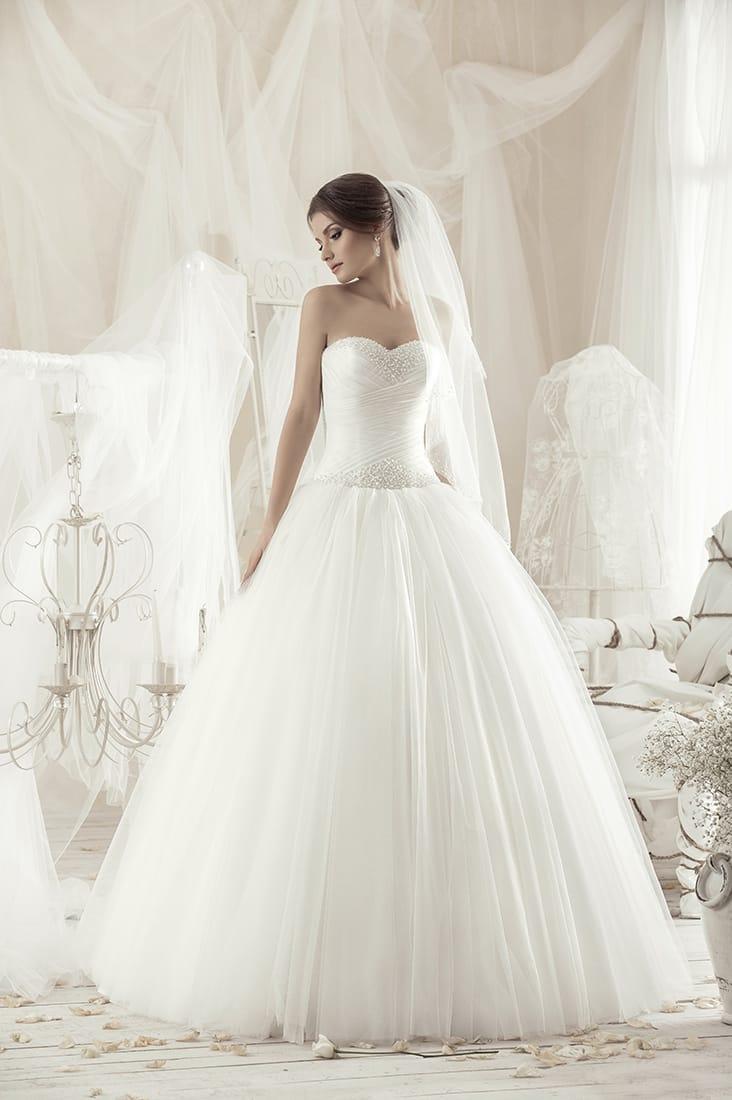 Изящное свадебное платье с драпировками на открытом корсете и романтичной юбкой пышного кроя.