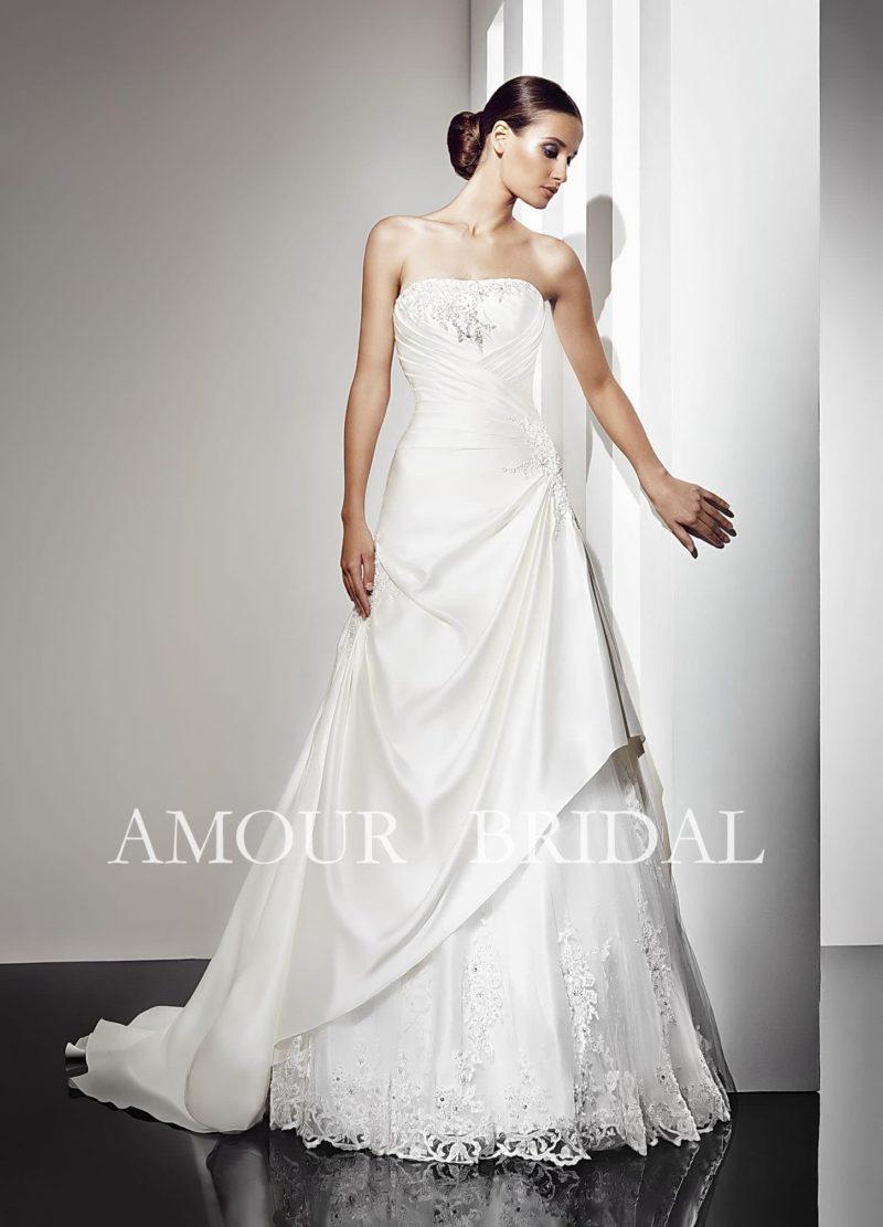 Атласное свадебное платье с открытым лифом прямого кроя и красивыми складками ткани на юбке.