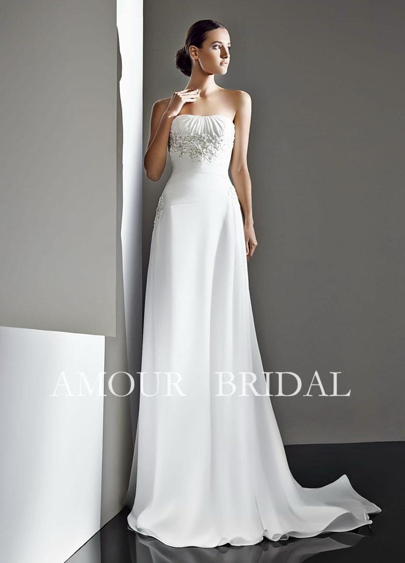 Деликатное свадебное платье с открытым лифом, украшенным драпировками, и небольшим шлейфом.