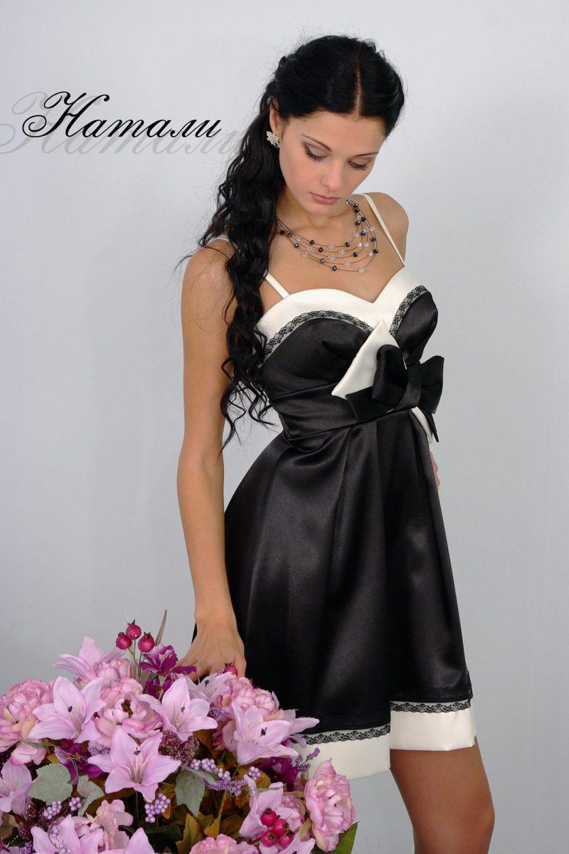 Черное вечернее платье из атласной ткани, украшенное бантом.
