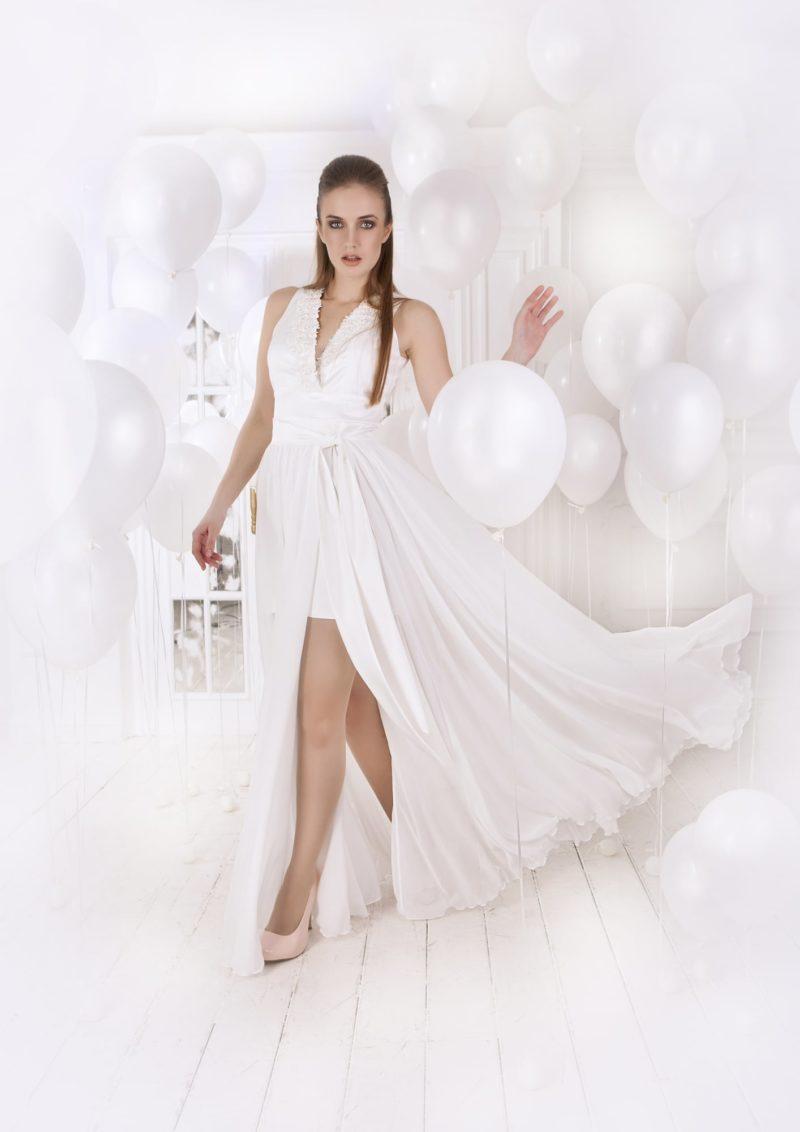 Стильное вечернее платье с двойной юбкой, смелым разрезом по подолу и V-образным декольте.