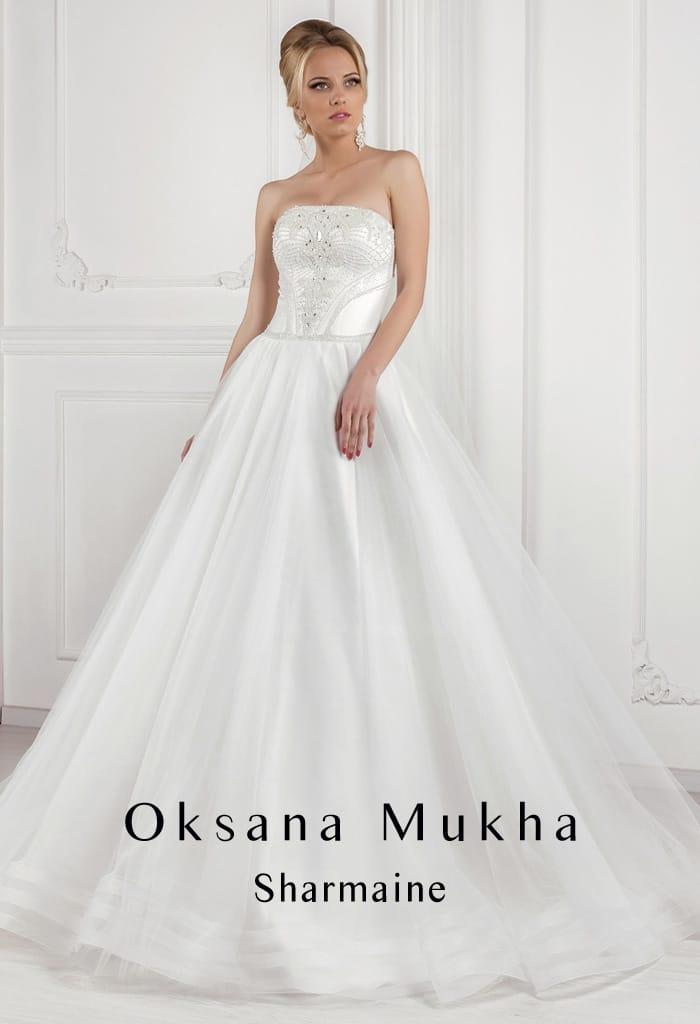 Лаконичное свадебное платье пышного кроя из атласной ткани, с изящным прямым декольте.