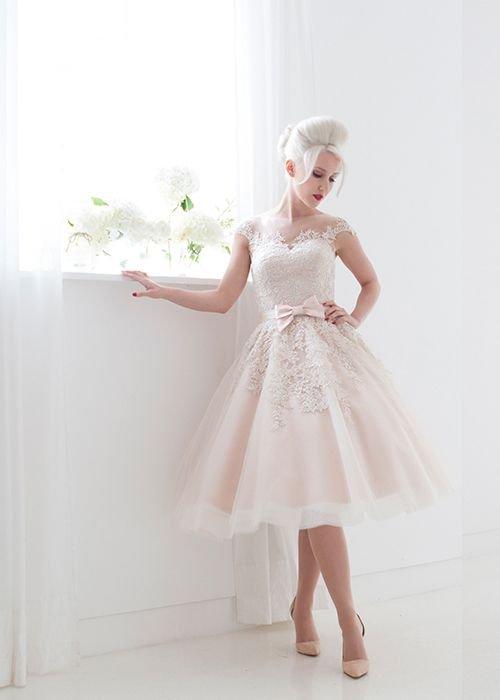 Розовое свадебное платье пышного кроя с поясом, украшенным бантом.
