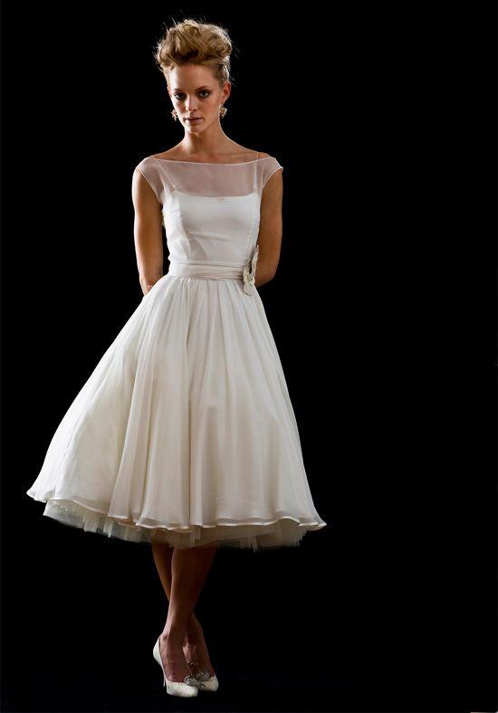 Короткое свадебное платье с полупрозрачной отделкой закрытого верха.