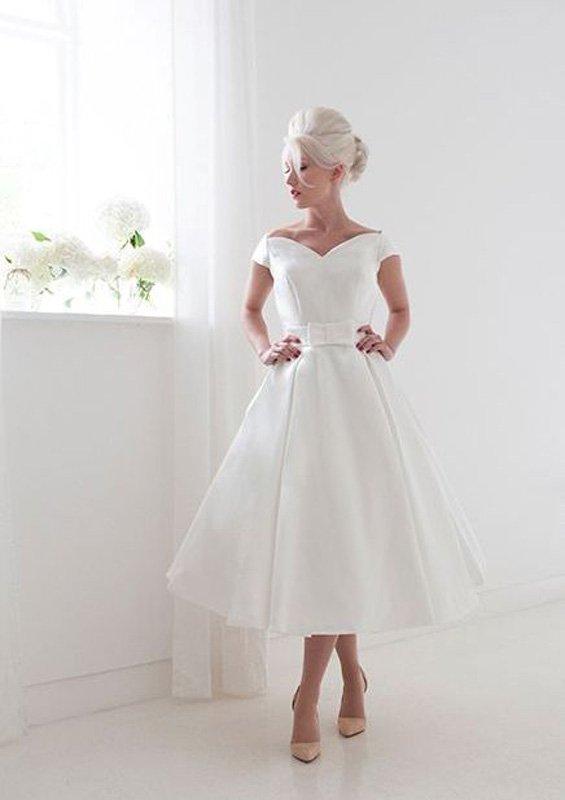 Свадебное платье с необычным вырезом и юбкой А-силуэта до середины икры.