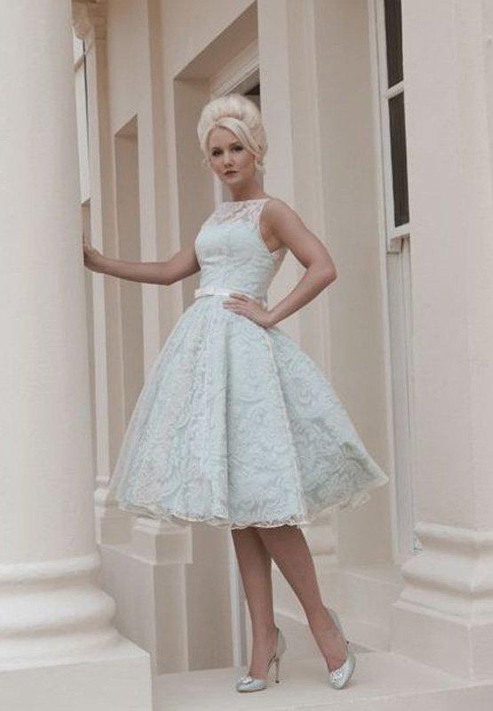 Пастельно-голубое свадебное платье с пышной юбкой до колена, покрытое кружевом.