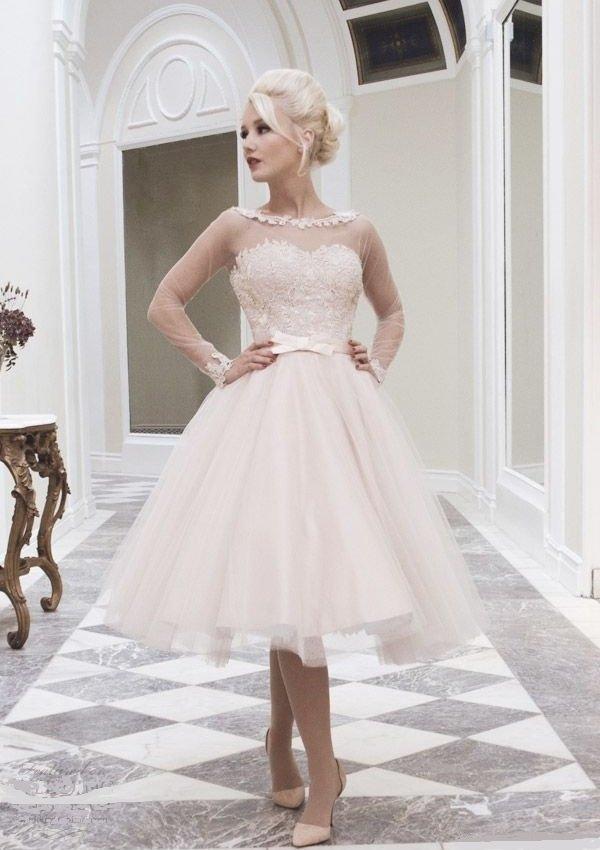 Короткое свадебное платье цвета слоновой кости с прозрачным рукавом.