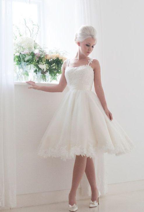 Изящное свадебное платье до колена с узкими бретелями и аппликациями на юбке.