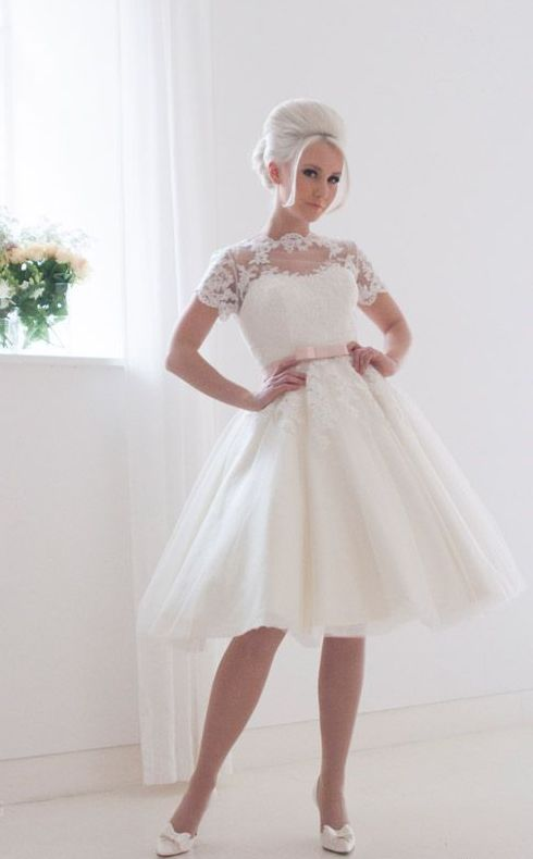 Пышное свадебное платье с коротким кружевным рукавом и розовым поясом.