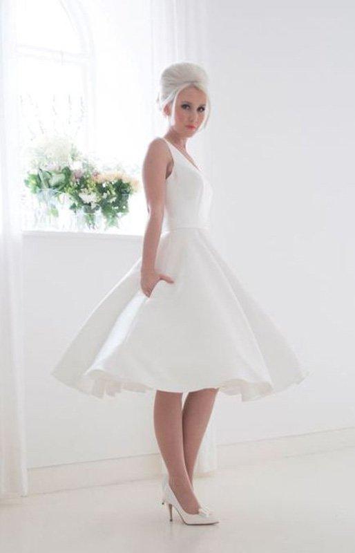Атласное свадебное платье до колена с лаконичным V-образным вырезом лифа.