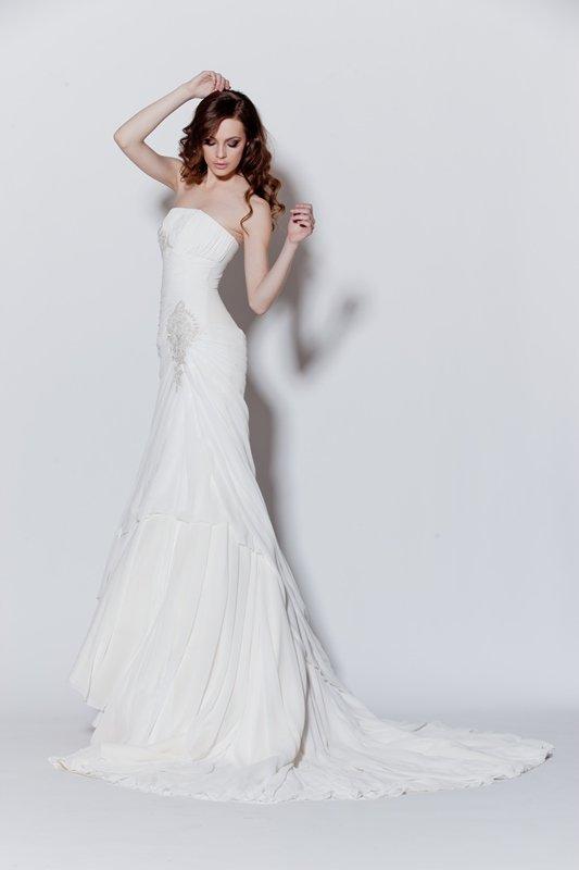 Прямое свадебное платье с волнами ткани по низу подола и шлейфу.