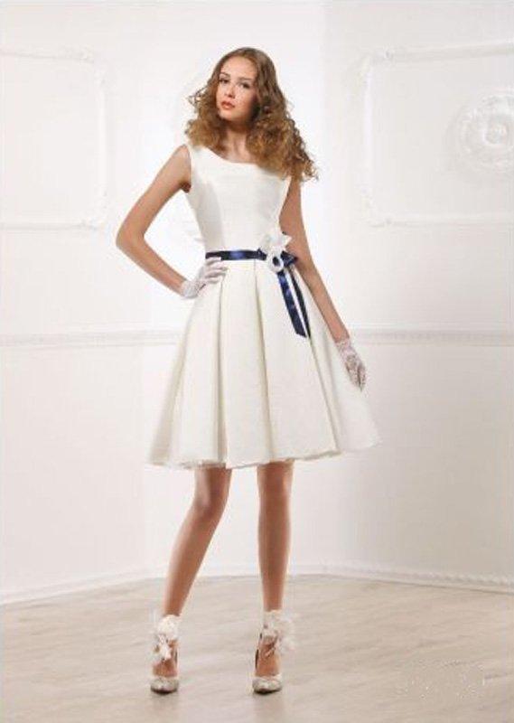 Атласное свадебное платье с вырезом бато и юбкой А-кроя до колена.