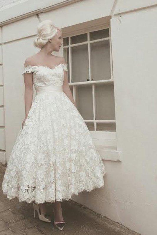 Короткое свадебное платье с бретелями на предплечьях и ажурным декором.