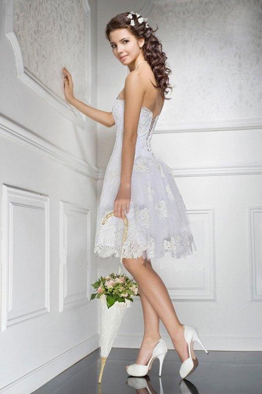 Необычное свадебное платье с короткой пышной юбкой, дополненной шлейфом.