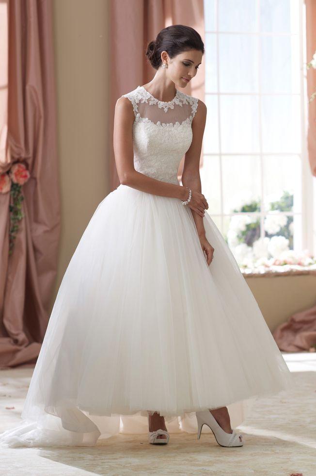 Пышное свадебное платье длиной до середины икры с кружевным лифом.