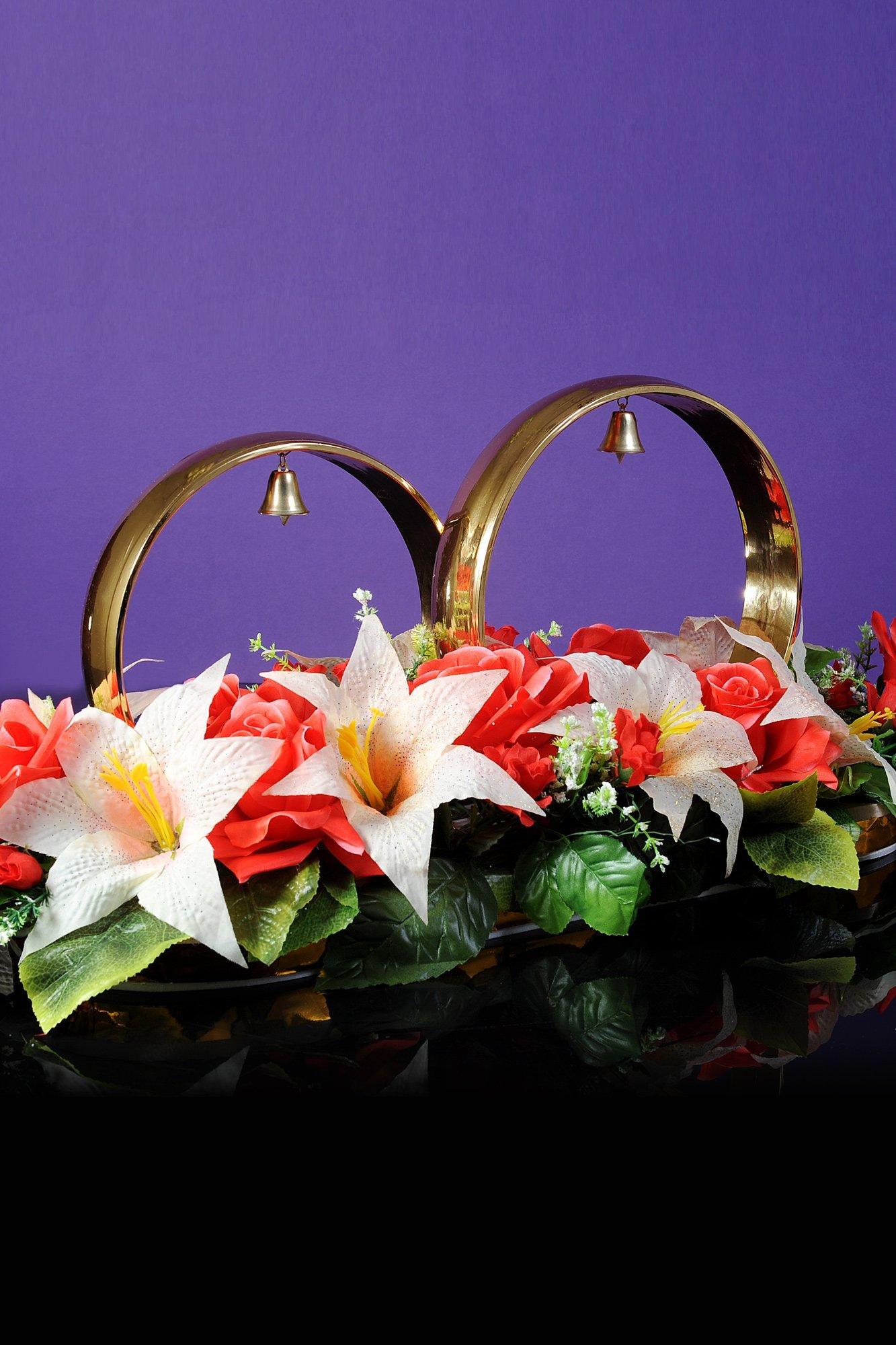 Золотистые свадебные кольца на машину, украшенные крупными цветами и колокольчиками.