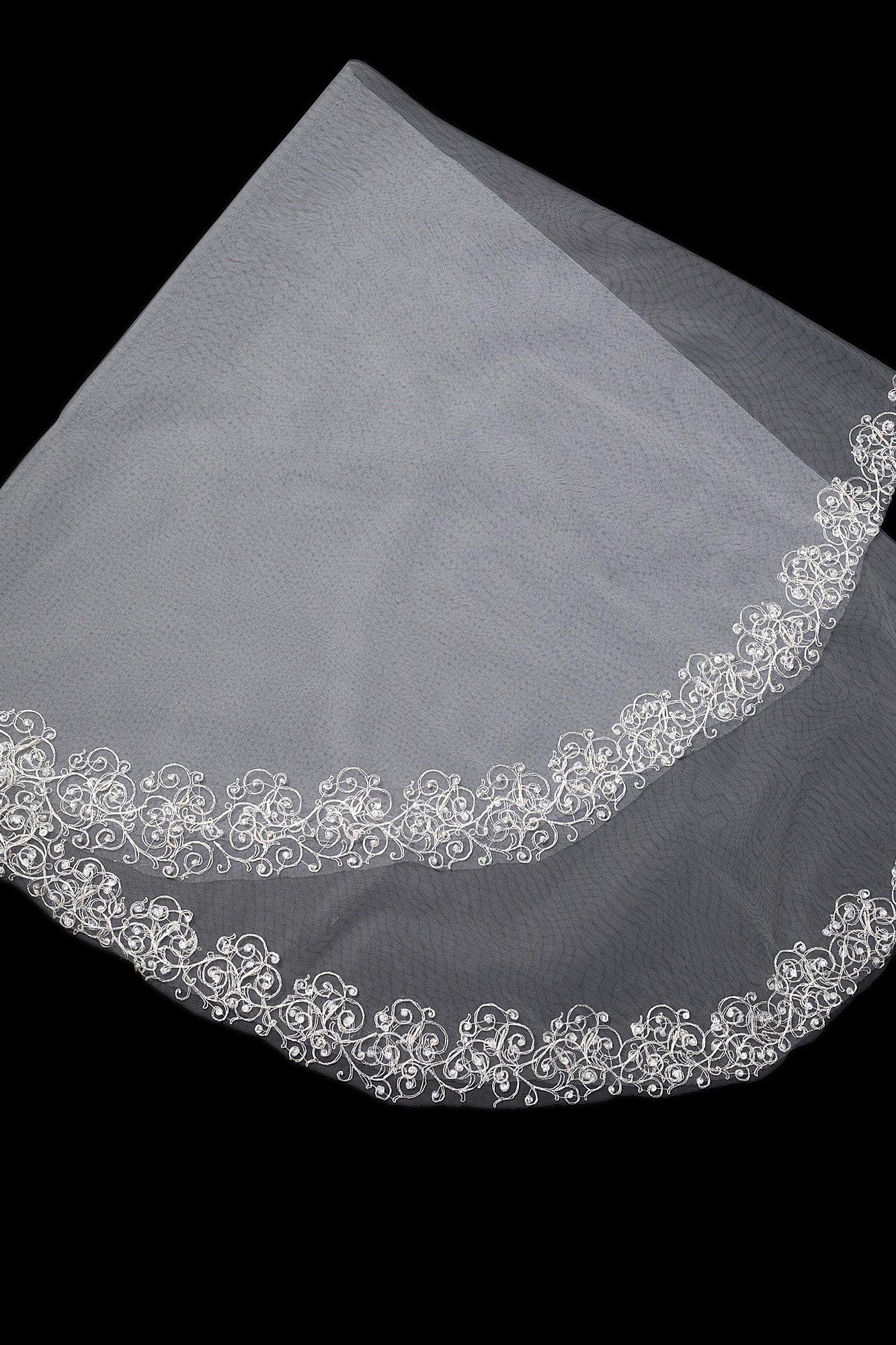 Романтичная белая фата, украшенная по краям вышивкой.