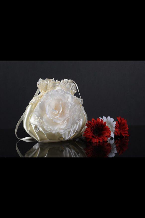 Кремового цвета свадебная сумочка из атласа, украшенная крупным бутоном спереди.