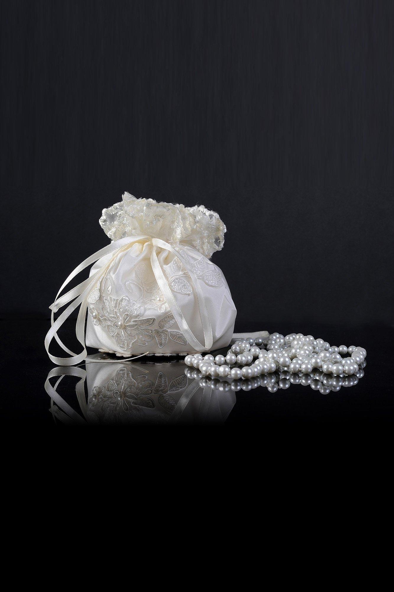 Небольшая свадебная сумочка оттенка слоновой кости, украшенная сверху кружевом.