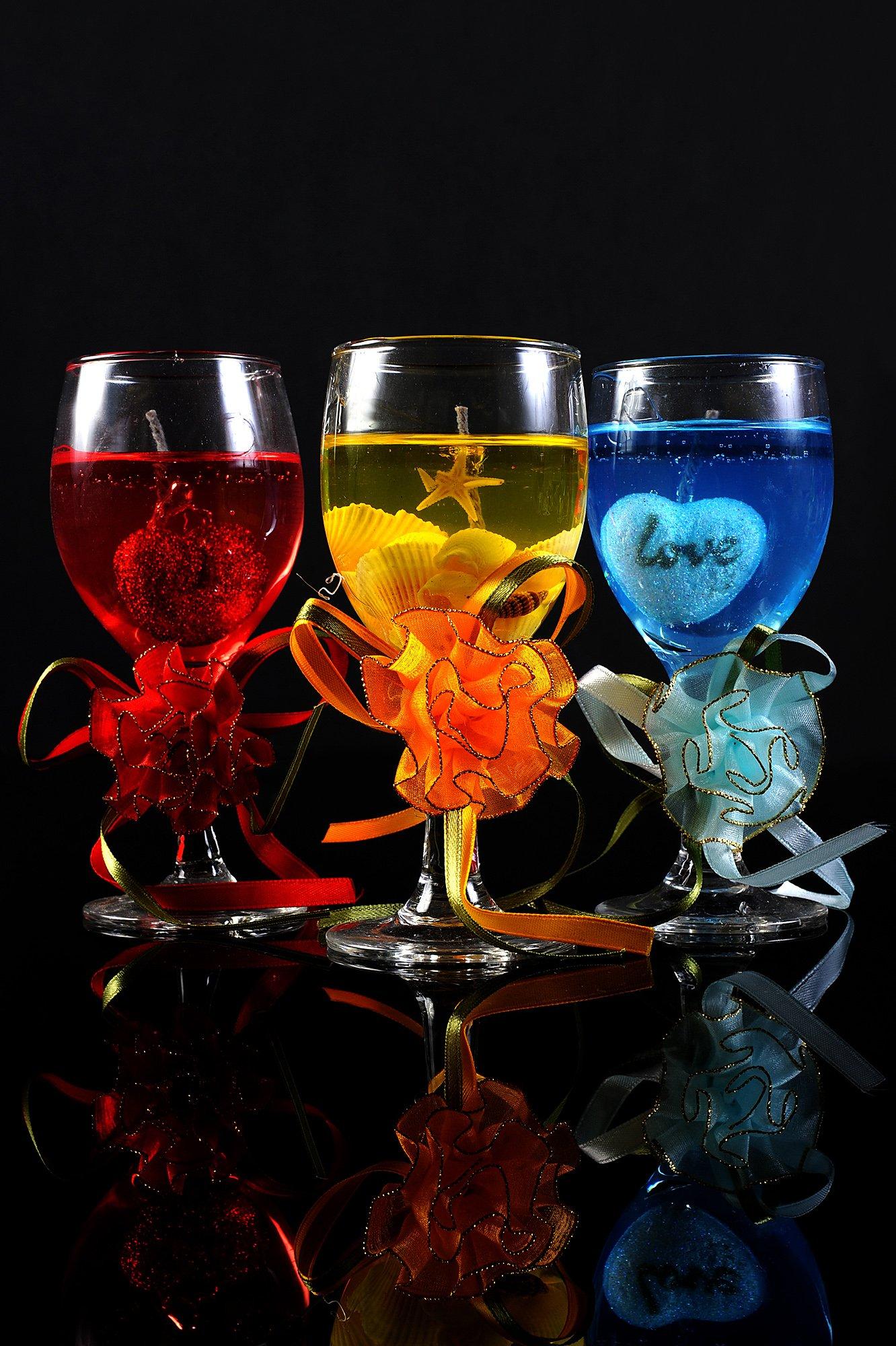 Полупрозрачная цветная свадебная свеча в бокале с пышной отделкой лентами.