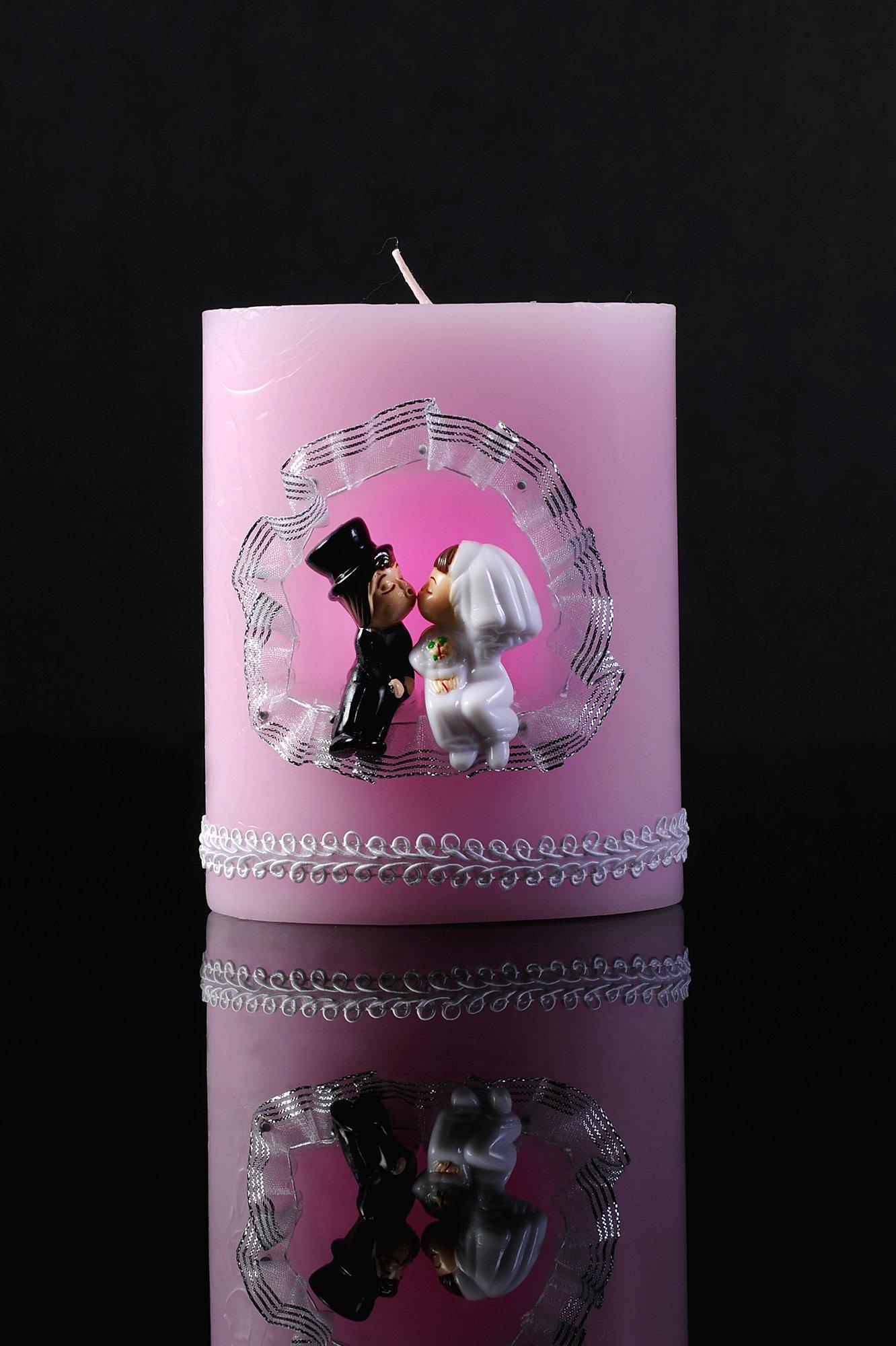 Небольшая свадебная свеча розового цвета с декором фигурками жениха и невесты.