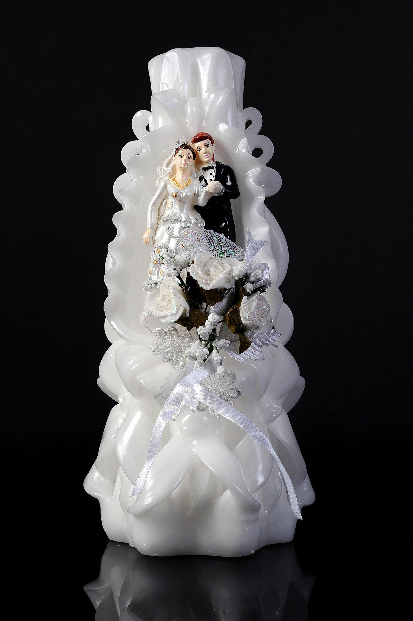 Белоснежная свадебная свеча, украшенная цветными фигурками жениха и невесты.