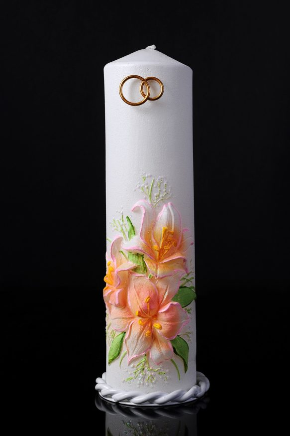 Белая свадебная свеча с цветным декором и золотыми кольцами сверху.