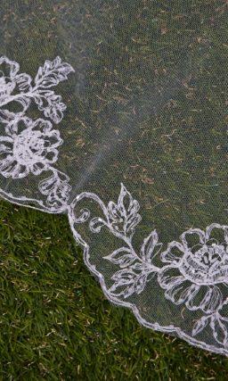 Длинная прозрачная фата с мелким цветочным рисунком по краю.