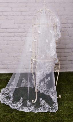 Классическая длинная фата белого цвета, украшенная кружевным узором по краю.