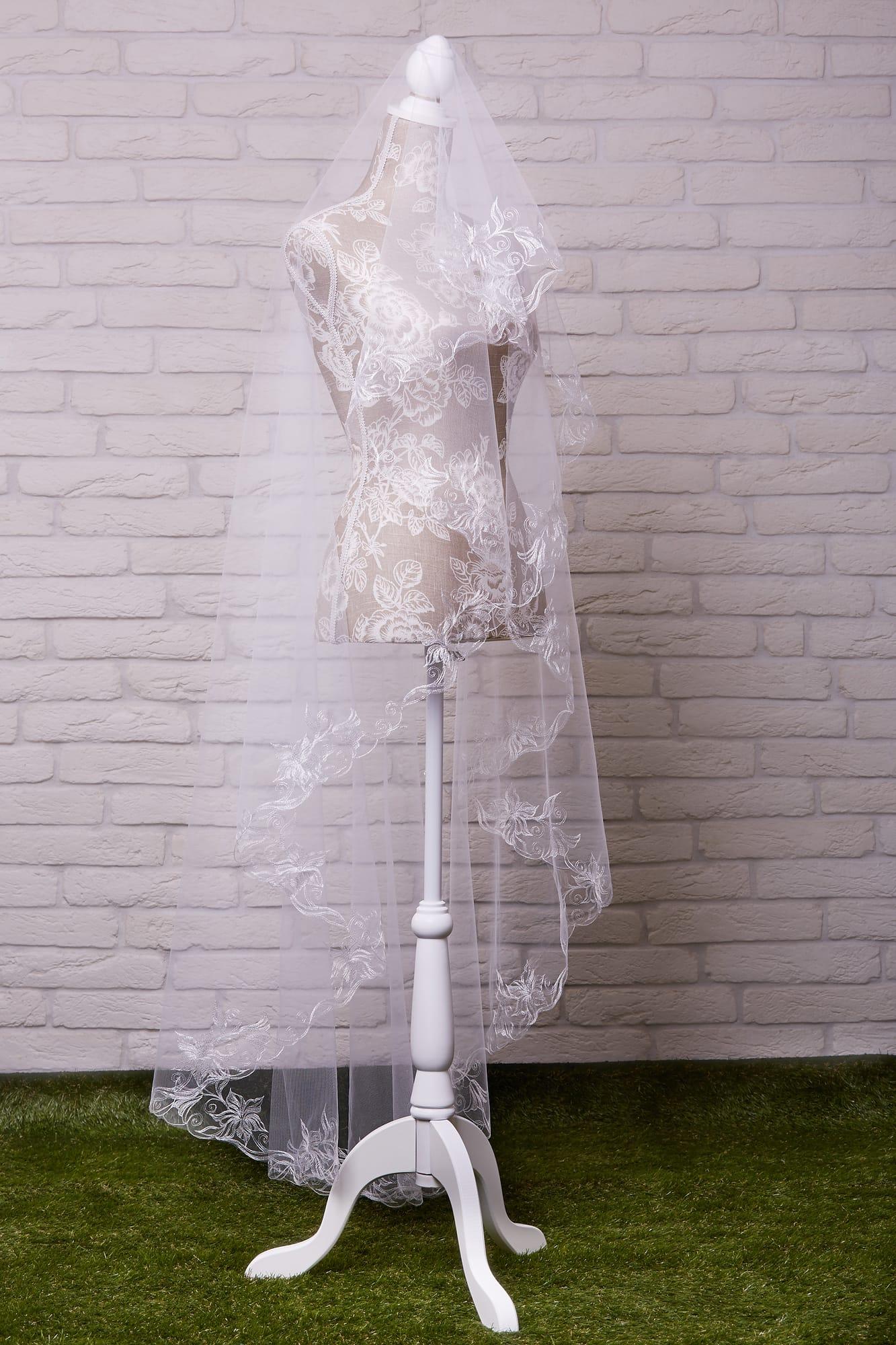 Полупрозрачная длинная фата, украшенная по краям деликатной вышивкой с крупным узором.