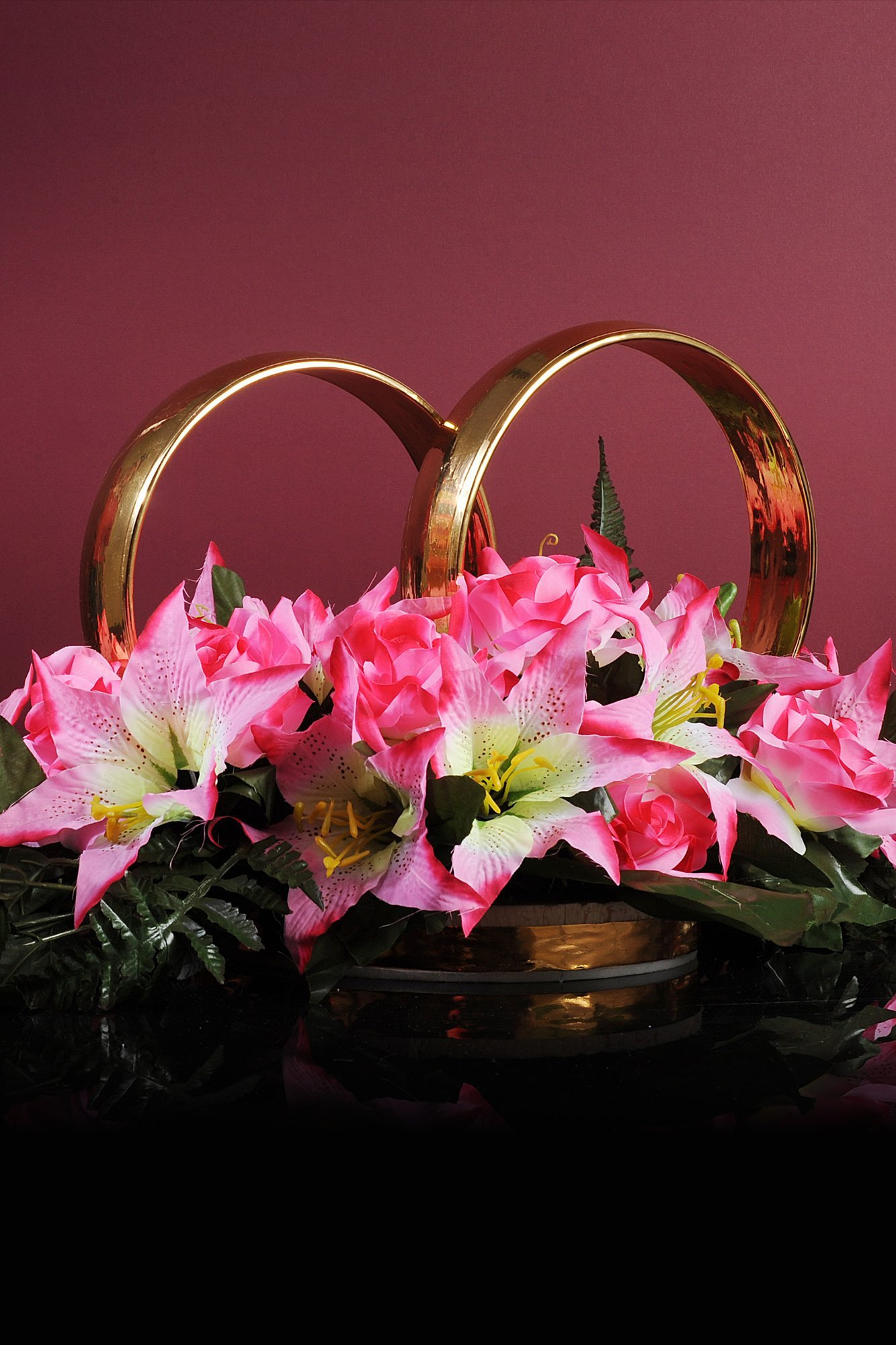 Свадебные кольца на машину, украшенные розово-белыми бутонами лилий.