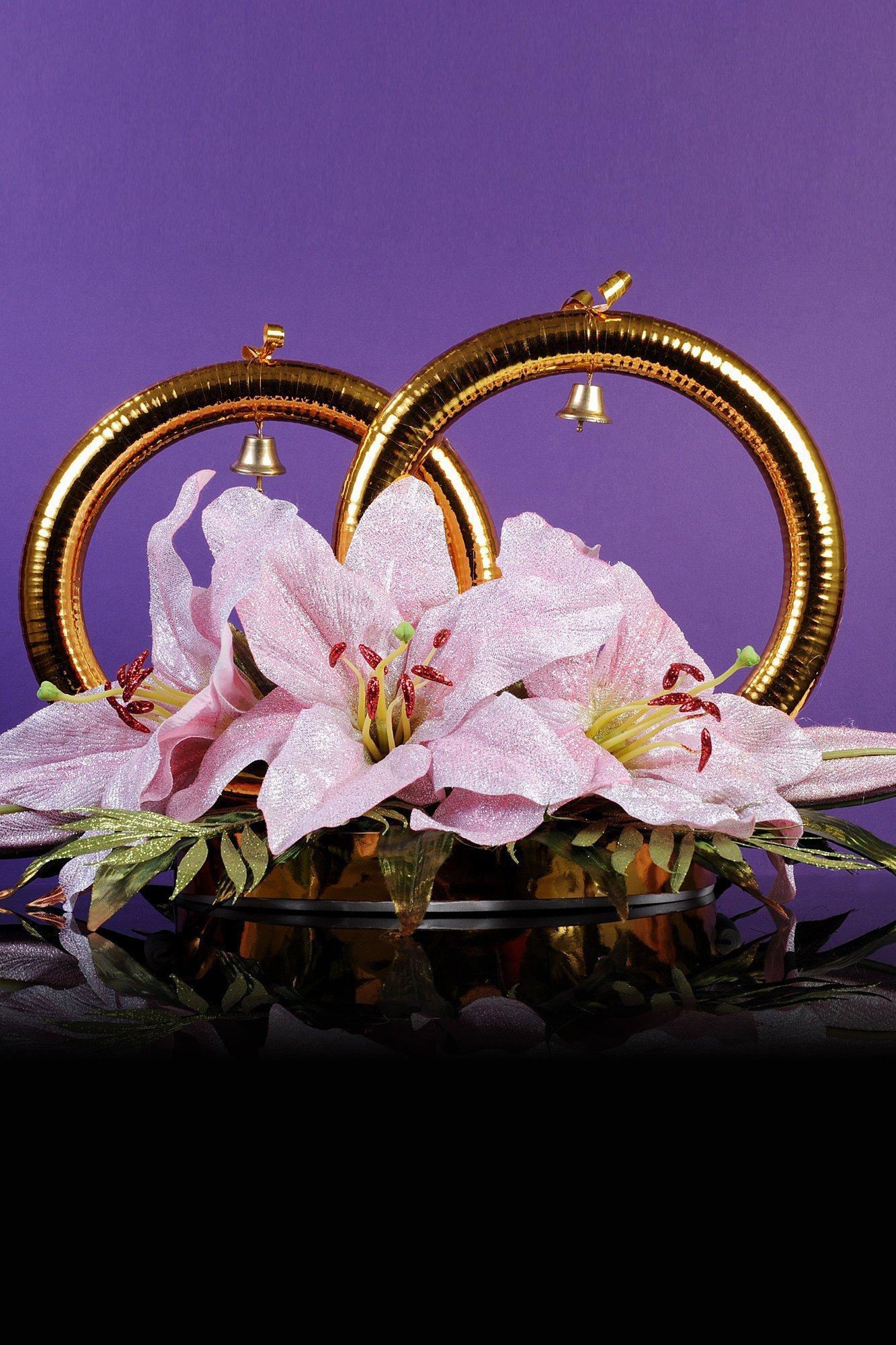 Золотистые свадебные кольца на машину, украшенные колокольчиками и цветочной композицией.