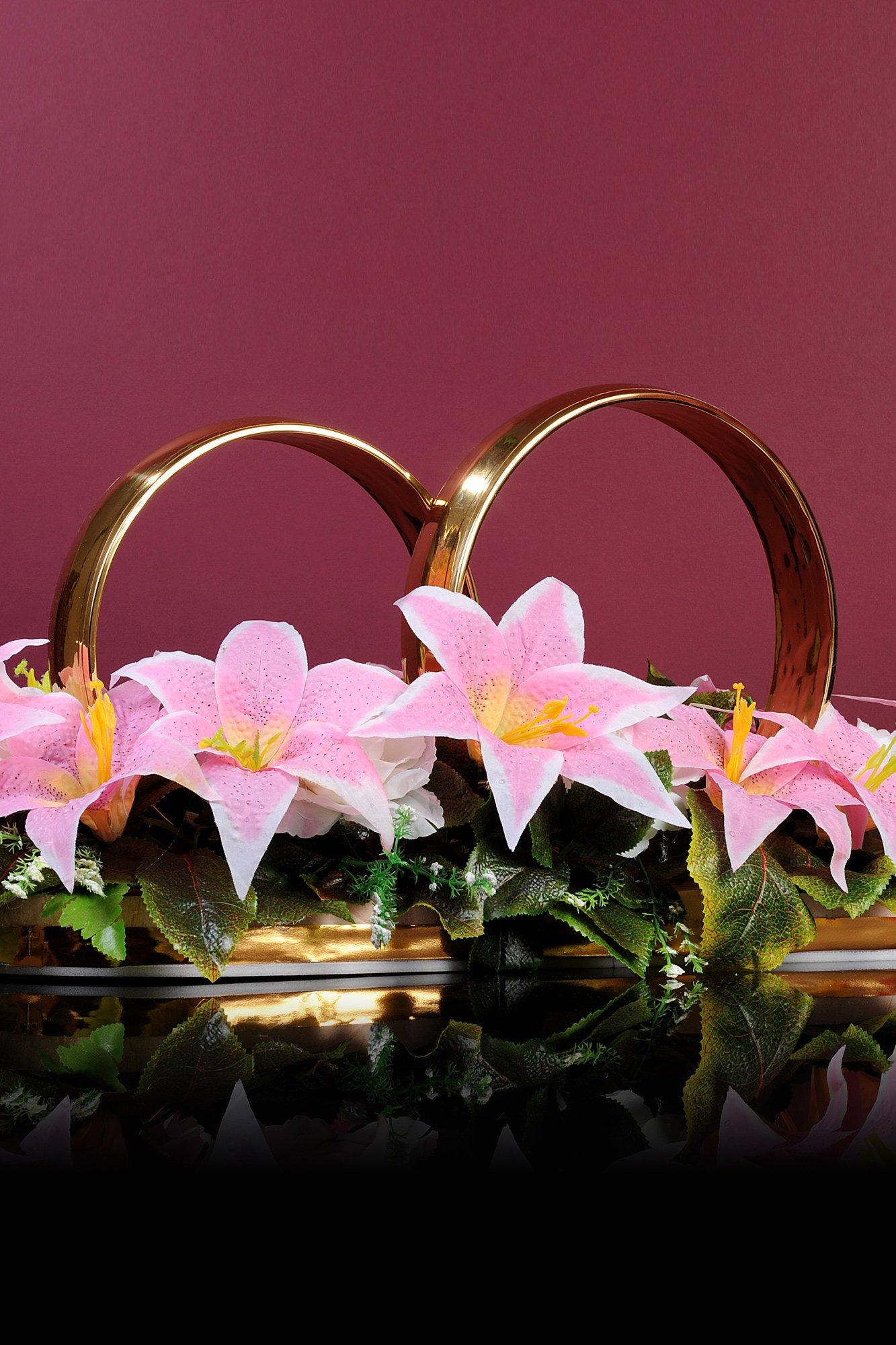Золотистые кольца на машину, украшенные розовыми бутонами лилий.