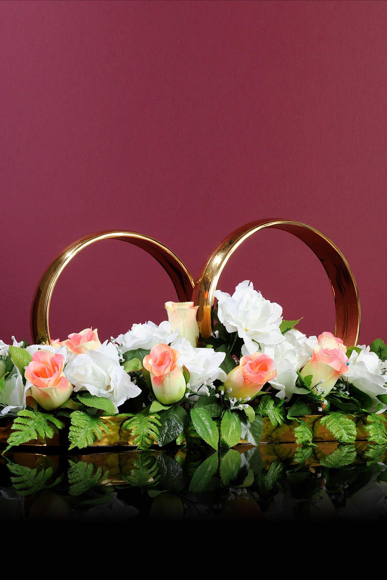 Золотистые кольца на машину, оформленные снизу розовыми и белыми бутонами.