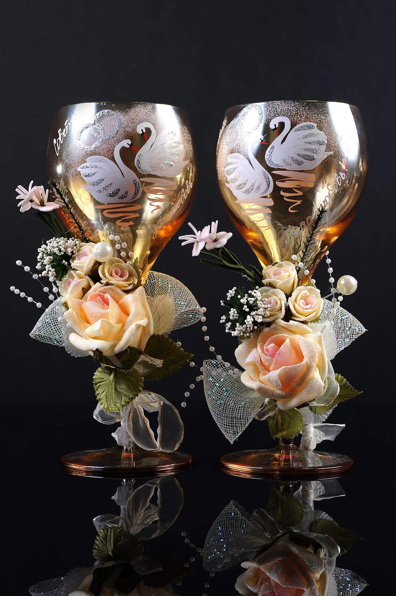 Золотистые свадебные бокалы с изображением лебедей и бежевыми бутонами.