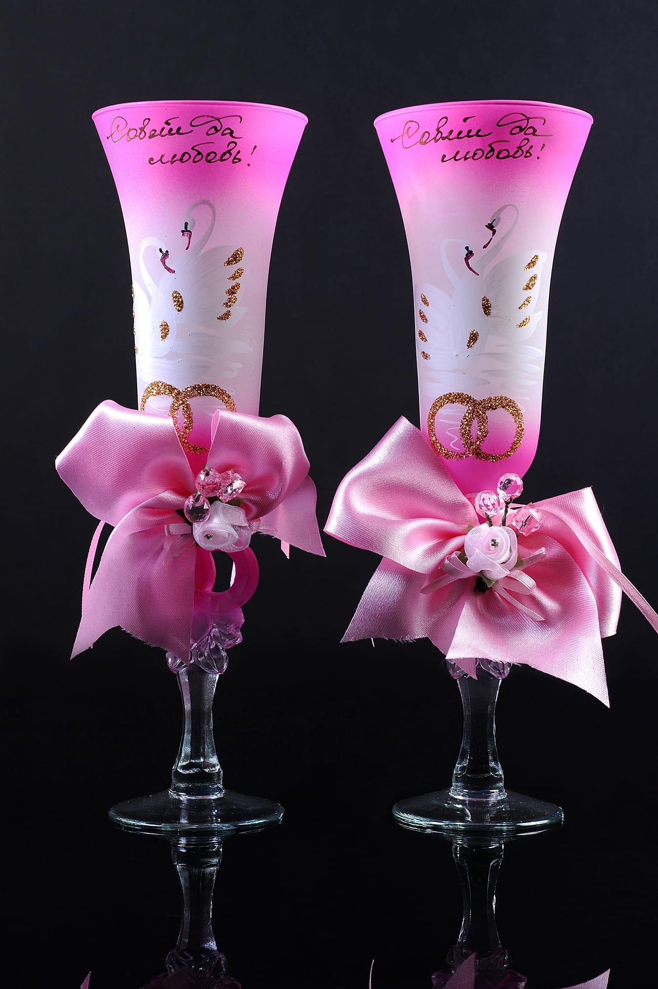 Цветные свадебные бокалы с изображением лебедей и объемными бантами на ножках.