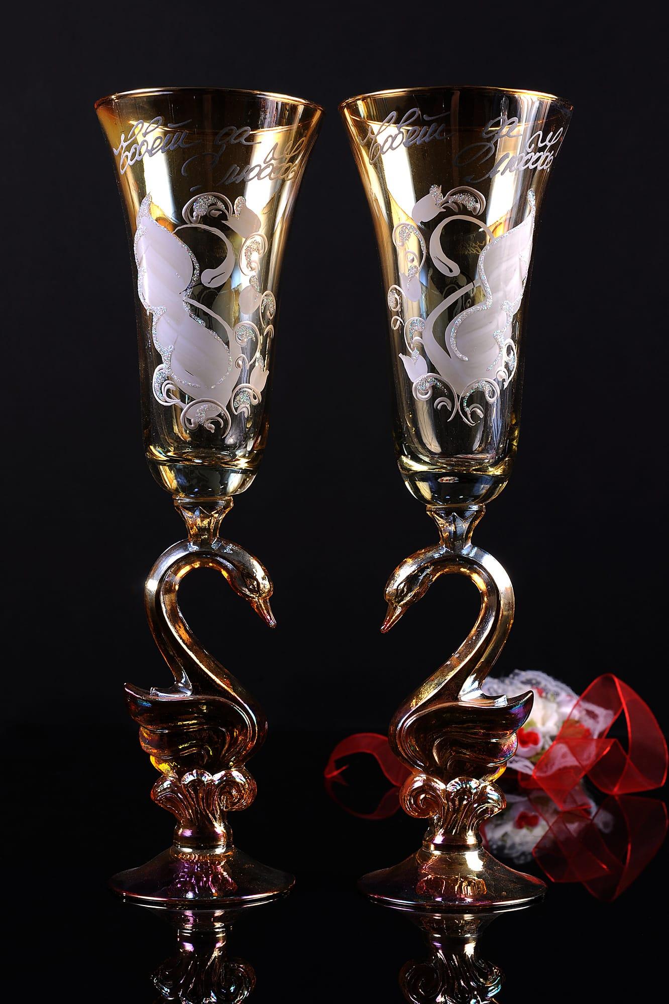 Золотистые свадебные бокалы с ножками в форме лебедей и цветным рисунком.
